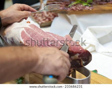 Cutting Crudo di Parma ham. Typical Italian delicatessen. Selective focus.  - stock photo