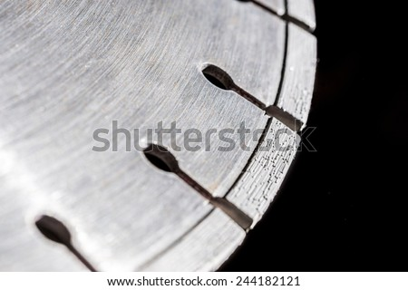 Cutting disk with diamonds, on black background.