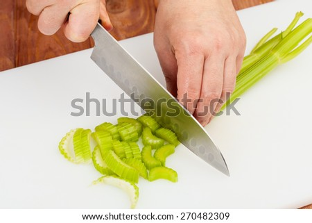 cutting fresh celery on a white cutting board closeup - stock photo