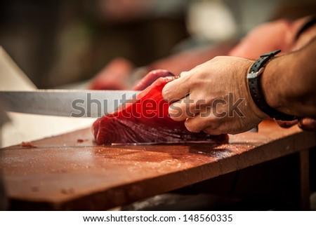 cutting fresh raw red tunna on fishmonger - stock photo