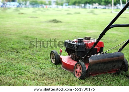cutting green grass with engine lawn mower