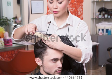 Cutting hair in beauty hairdressing salon. Portrait of handsome man having his hair cut by barber girl in beauty hairdressing saloon.