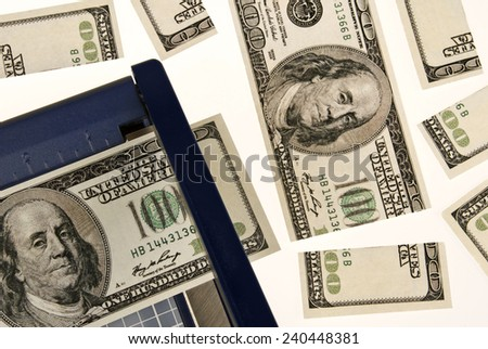 Cutting Hundred Dollar Bills/ Trimming Costs - stock photo