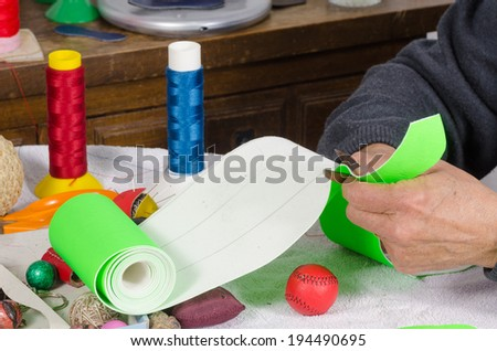 Cutting leather to  craft traditional  sport balls - stock photo