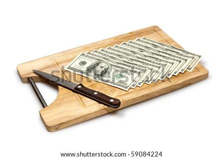 cutting money on board, dollars - stock photo