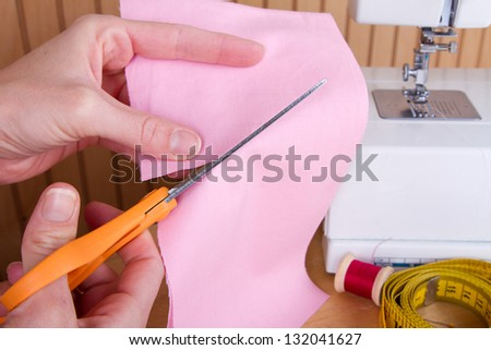 Cutting out a piece of pink fabric with scissors, sewing machine in background