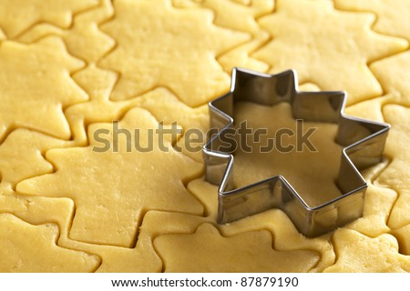 Cutting out Christmas cookies from shortcrust dough with a Christmas tree shaped cutter (Selective Focus, Focus on the two lowest edges of the cutter)