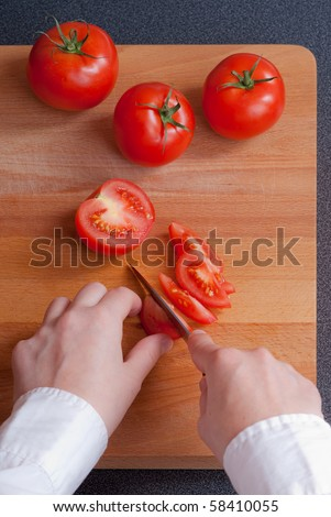 Cutting red tomato on wooden board.