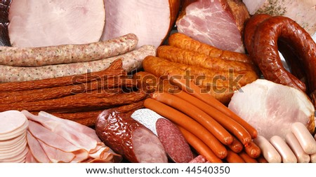 Cutting sausage and meat on a celebratory table. - stock photo
