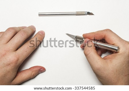 Cutting something out of paper. - stock photo