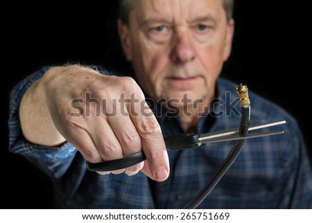 Cutting the cable connection to coax connector illustrating retired people canceling cable TV service