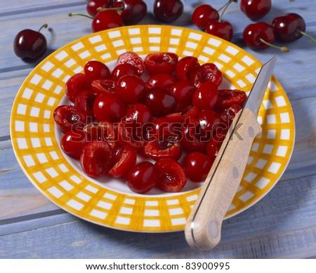 Cutting the cherries in half - stock photo