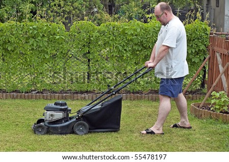 Cutting the grass to size with the mower in the garden at a spring time