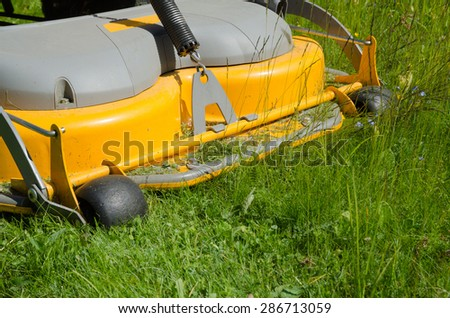 Cutting the lawn with a riding lawn-mower - stock photo
