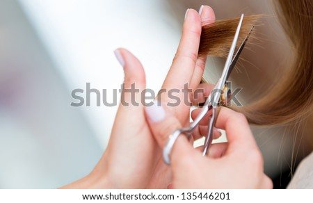 Cutting the split ends of damage hair at the beauty salon - stock photo