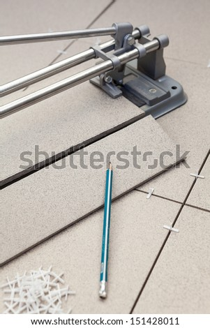 Cutting tiles with tile-cutter when laying floor - stock photo