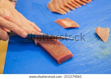 cutting tuna steak, fish raw preparing - stock photo