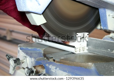 Cutting Window Frame Profile. Circular saw cutting window profile. - stock photo