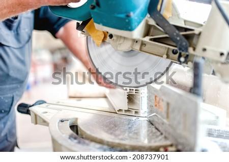 Cutting Window Frame Profile. Circular saw or sliding compound mitre saw cutting window profile. - stock photo