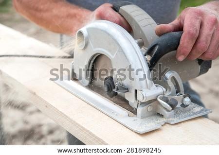 Cutting wood hand power saw - stock photo