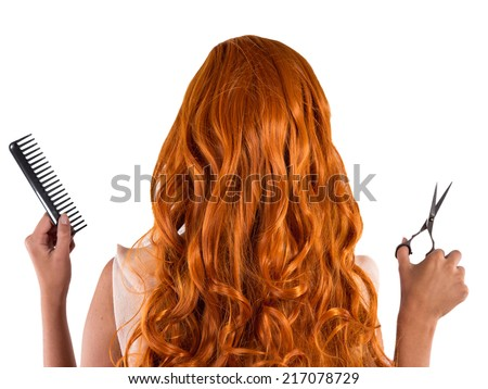 cutting young beautiful brunette woman's hair with scissors