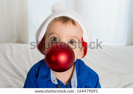 cuttle little kid in Santa Claus hat playing with Christmas Bubble in Mouth - stock photo