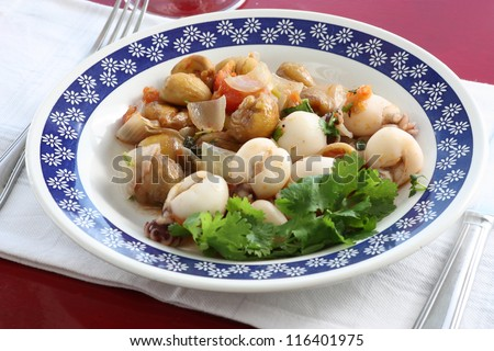 Cuttlefish dish with chestnuts and tomatoes. - stock photo