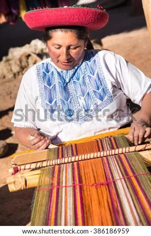 CUZCO, PERU - CIRCA 2015: An unidentified woman weaves fabric on a loom circa 2015 in Cuzco, Peru. - stock photo