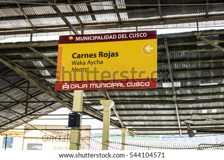 CUZCO, PERU - OCTOBER 13, 2016: Sign suspended from the roof in Spanish, Quechua and English to indicate red meat section of the San Pedro market in the city of Cuzco.