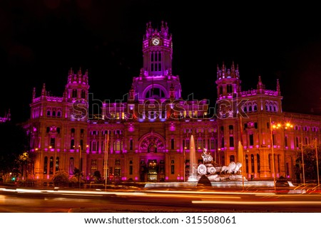 Cybele Palace at the Plaza de Cibeles with light trails of the traffic at night, Madrid, Spain. Purple and red illumination, Cybele fountain, dark sky  - stock photo