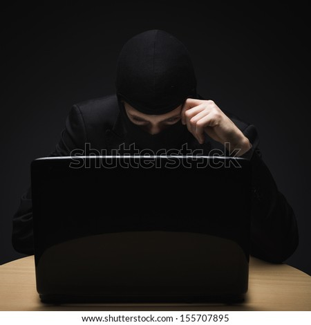Cyber crime as a hacker disguised in a balaclava sits in the darkness behind a laptop computer stealing personal or business information - stock photo