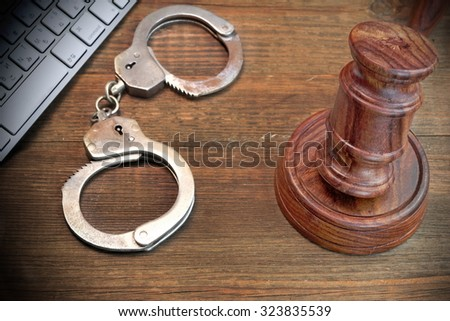 Cyber Crime Concept, Judges Gavel Computer Keyboard  And Real Handcuffs On The Rough Brown Wood Table - stock photo