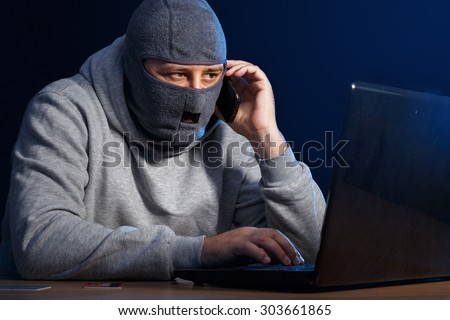 Cyber criminal hacking into a computer. Stealing information and talking on the phone - stock photo