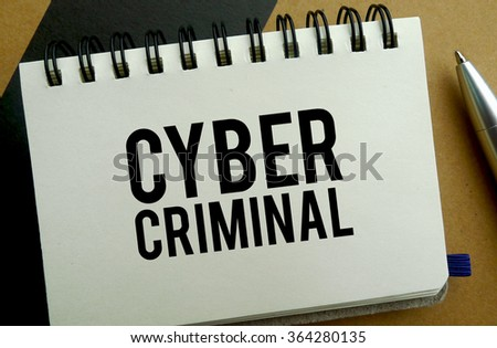 Cyber criminal memo written on a notebook with pen - stock photo