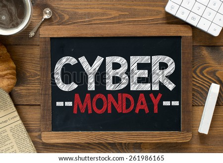 Cyber monday handwritten on blackboard. Cyber monday handwritten with white chalk on a blackboard, cup of coffee ,croissant, newspaper and calculator on wooden background - stock photo