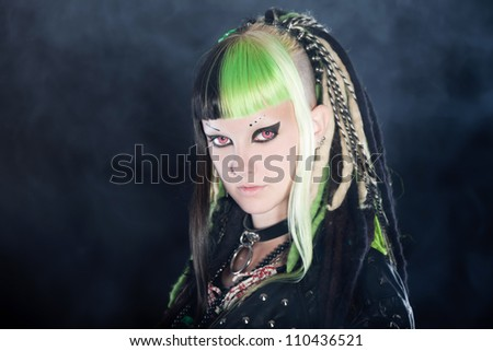 Cyber punk girl with green blond hair and red eyes isolated on black background with smoke. Expressive face. Studio shot.