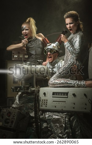 Cyberpunk. Future. Fantasy story. Two girls and a man firing a weapon of the future. - stock photo