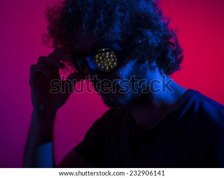 Cyborg man in shadows with red backdrop and blue key light, with bionic led eye - stock photo