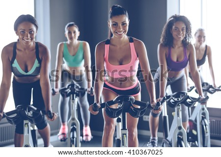 Cycling beauties. Young beautiful women with perfect bodies in sportswear looking at camera with smile while cycling at gym - stock photo