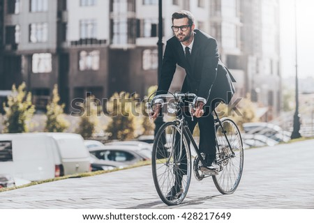 Cycling by the street. Full length of handsome young businessman looking forward while riding on his bicycle - stock photo