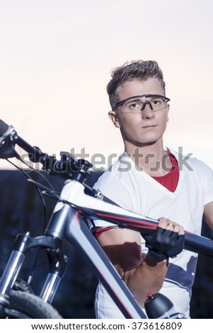 Cycling Concept and Ideas. Handsome Sportive Caucasian Cyclist With MTB Bike Outdoors. Vertical Image - stock photo