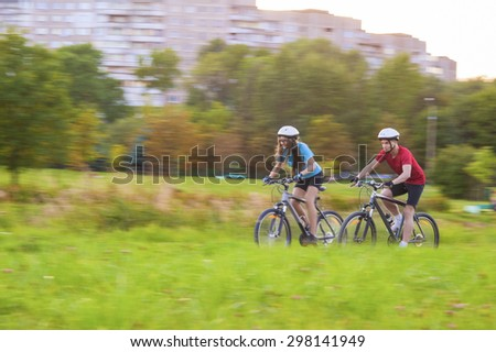 Cycling Concept: Young Caucasian Couple Having a Speedy Bicycle Trip Outdoors. Blurred Motion Due to Paning. Horizontal Image Composition - stock photo