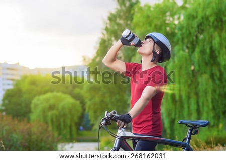 Cycling Concept: Young Caucasian Male Cyclist Having water Break Outdoors and Holding Mounting Bike.Horizontal Image Composition