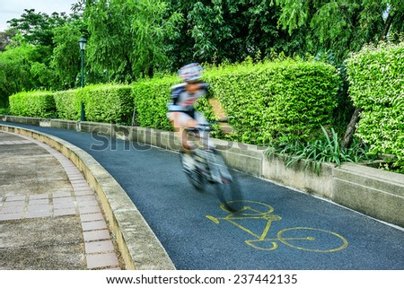 Cycling on bicycle lane in city park, Blurred motion. - stock photo