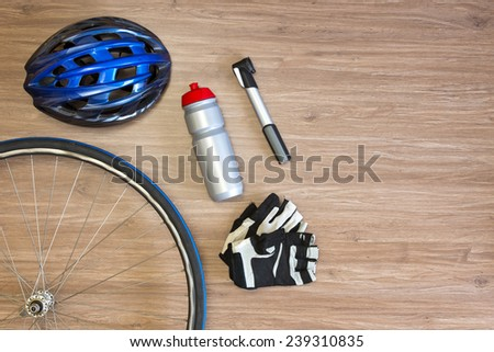 Cycling sports items arranged on a wooden background, seen from above. Items include a sports helmet, spoked wheel, drinking bottle, lightweight air pump and gloves - stock photo