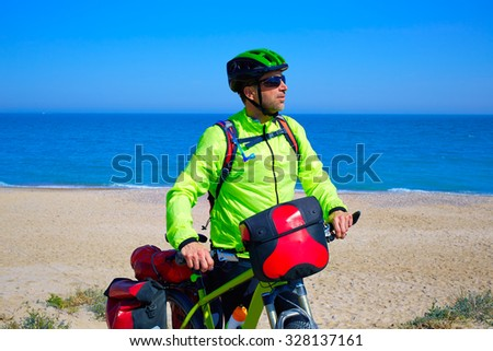 cycling tourist MTB cyclist in Mediterranean beach with panniers and saddlebag - stock photo