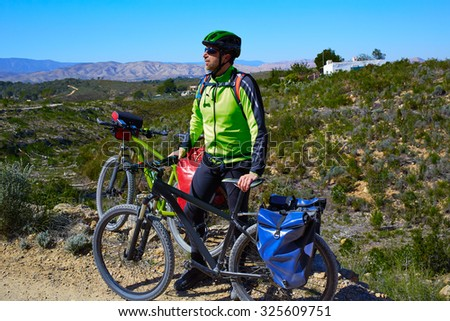 cycling tourist MTB cyclist in Pedralba Valencia with paniers and saddlebag Spain