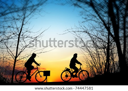 Cycling trip at sunset - stock photo