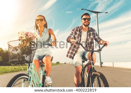 Cycling with fun. Low angle view of cheerful young couple smiling and riding on bicycles  - stock photo