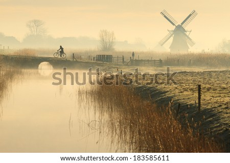 Cyclist and a foggy, spring sunrise in the Dutch countryside. - stock photo